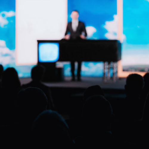 Presentation of a Speaker on the Stage Silhouette Speaker Stage Audience Presentation Media Press Conference Communication Public Event Technology Speech Meeting Seminar Politician Politics Entertainment Bussiness Government Corporate Live Leadership Campaign Correspondent Broadcast Square Watching Crowd Rear View Video Unrecognizable Person