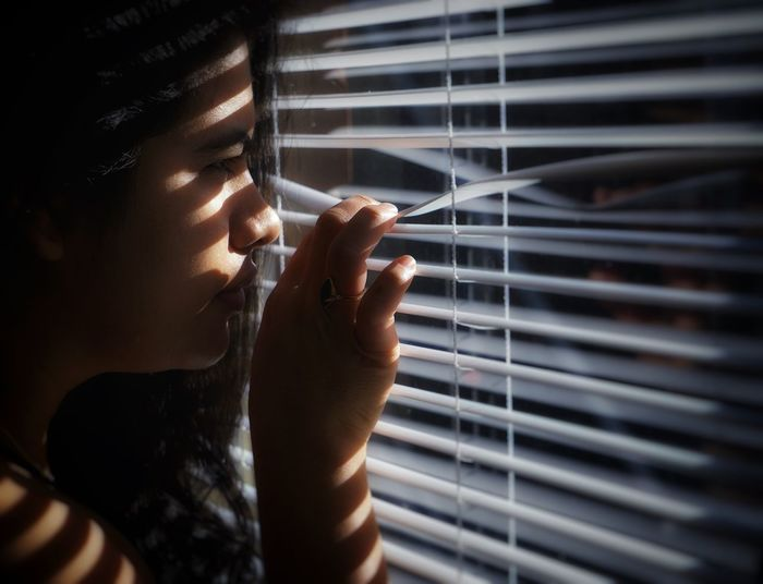 Close-up of woman looking through window blinds