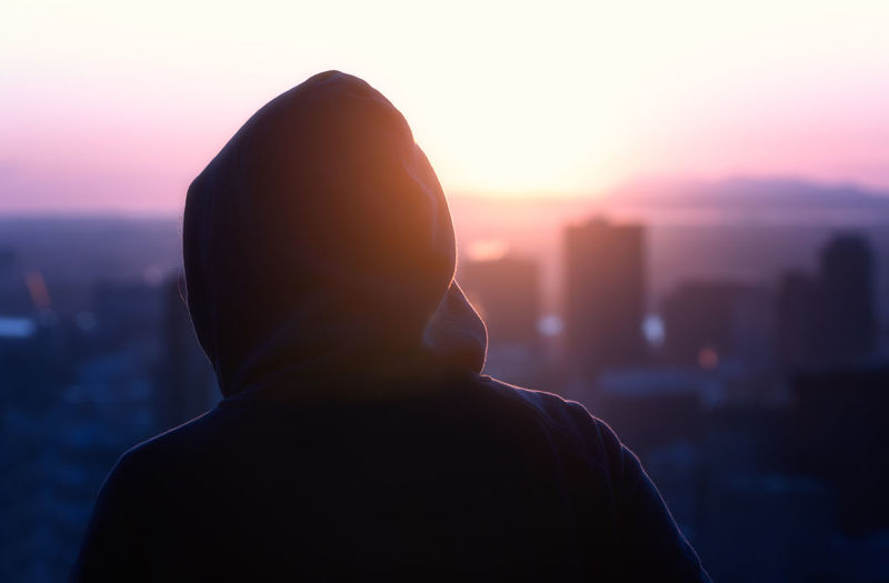 Close-up of silhouette person wearing hooded shirt against sky during sunset