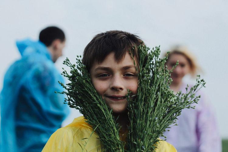 Portrait Of Happy Boy Holding Plants