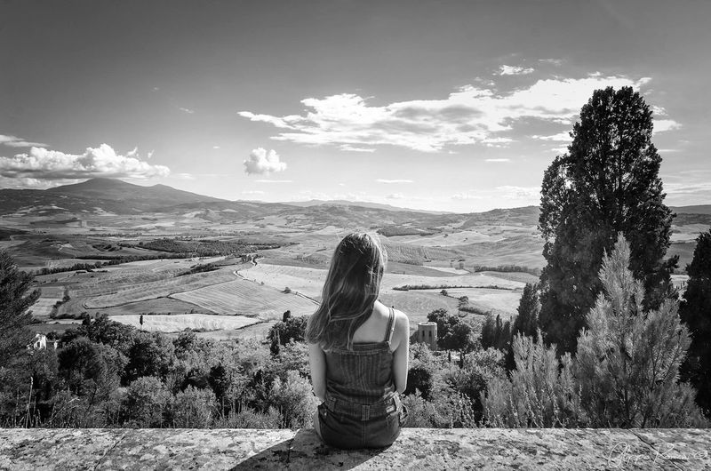 Rear View Of Young Woman Sitting On Retaining Wall At Val D Orcia