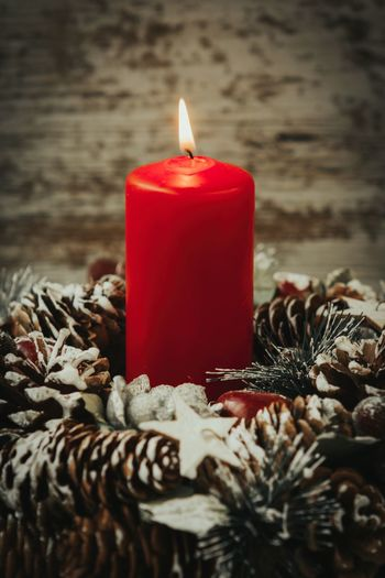Close-up of candle with pine cone on table