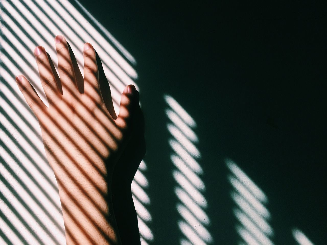 Cropped image of woman hand on wall in shadow pattern