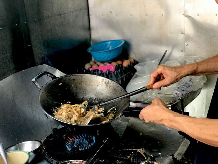 Midsection of man cooking food in kitchen