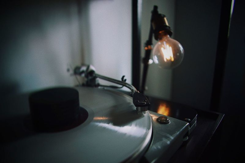 Close-up of illuminated light bulb by turntable