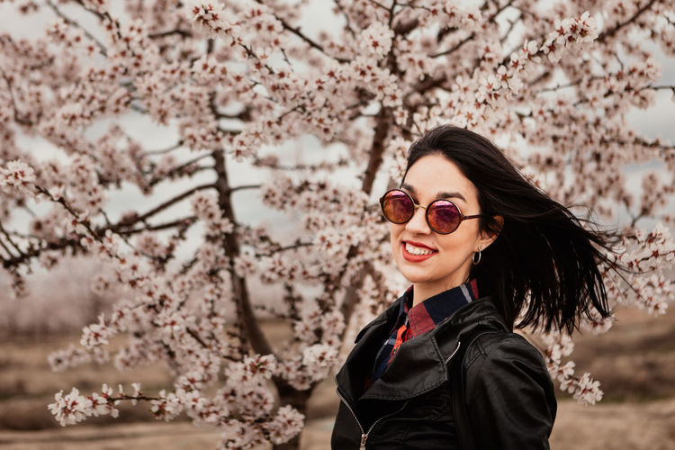 Portrait of young woman wearing sunglasses standing against cherry tree