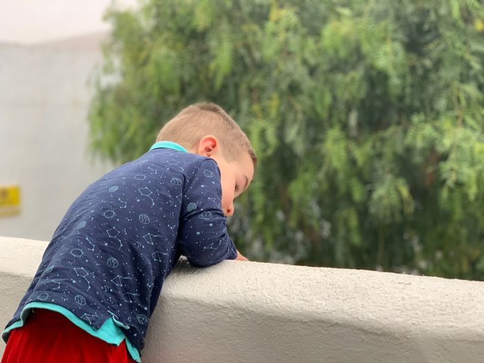Side view of boy leaning on concrete wall