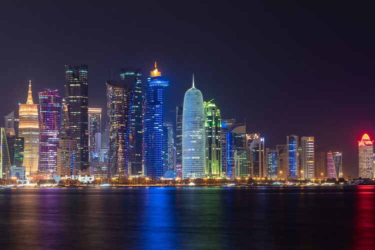 Doha, Qatar Building Exterior Built Structure Architecture Night City Building Illuminated Office Building Exterior Water Skyscraper Waterfront Landscape Urban Skyline Reflection Sky Modern Cityscape Sea Travel Destinations Tall - High No People Outdoors Financial District  Nightlife Doha Qatar Middle East Travel