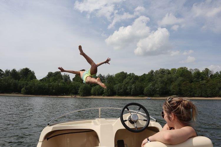 Teenage Boy And Girl In Sea Against Sky