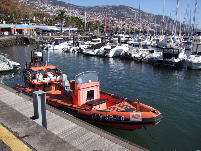 Life Saving Boat Composition Funchal Lifeboat Madeira Madeira Island Portugal Sunlight Blue Sky Boat Boats Harbor High Angle View Lifeboat RNLI Mode Of Transport Moored Mountain Nautical Vessel No People Outdoor Photography Reflections In The Water Ripples In The Water Sea Transportation Water Waterfront