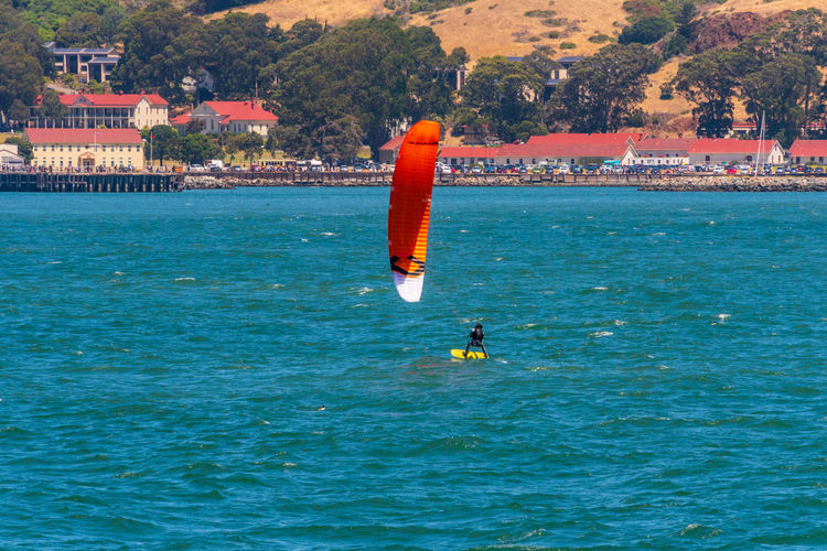 Water Waterfront Sea Sport Adventure Aquatic Sport Real People One Person Nature Leisure Activity Day Unrecognizable Person Lifestyles Orange Color Extreme Sports Men Motion Outdoors Skill  Windsurfing