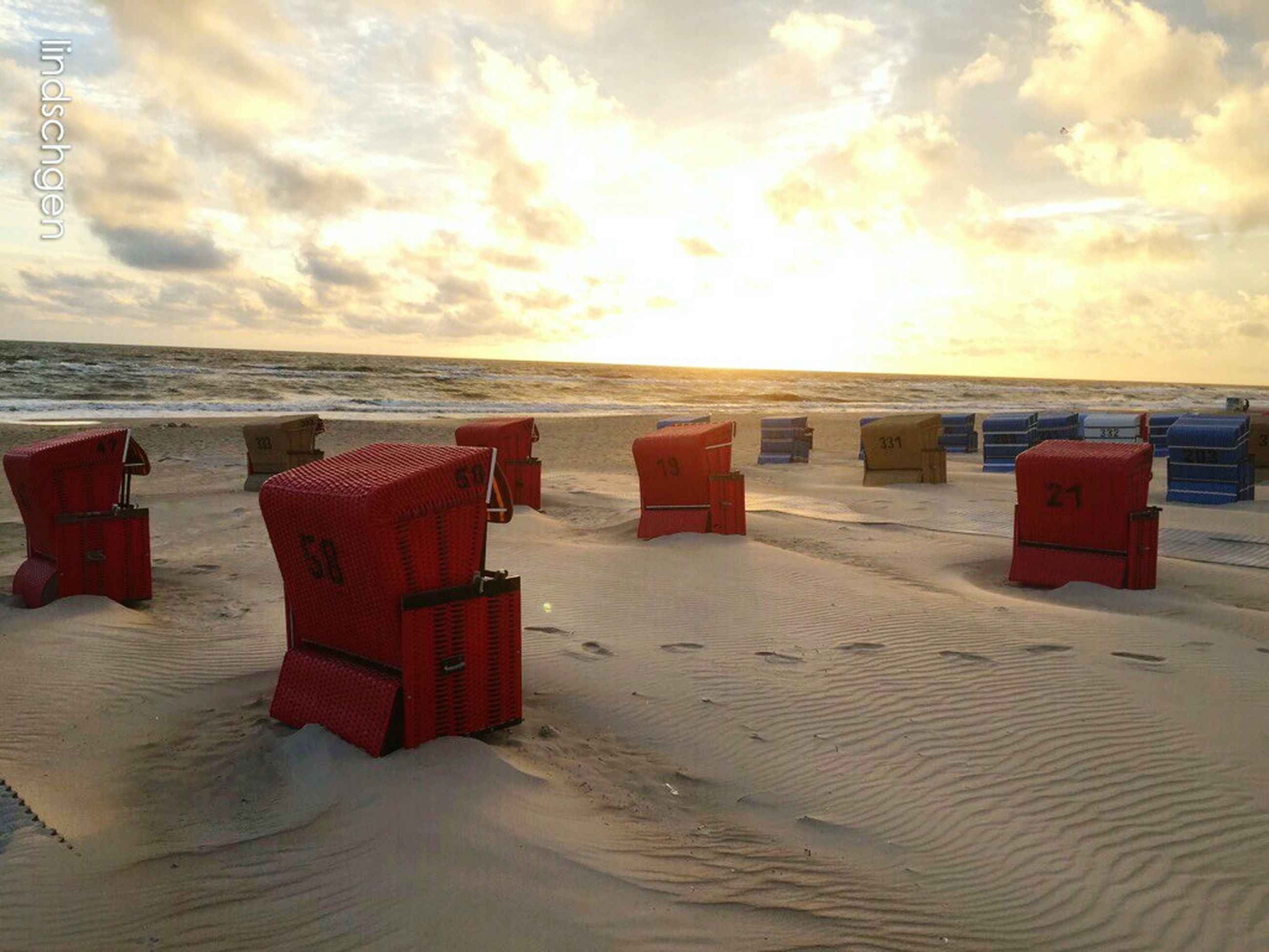beach, sand, horizon over water, sea, sunset, hooded beach chair, tranquility, sky, tranquil scene, scenics, water, cloud, beauty in nature, cloud - sky, shore, nature, sandy, majestic, outdoors, non-urban scene, vacations, calm, boardwalk, coastline