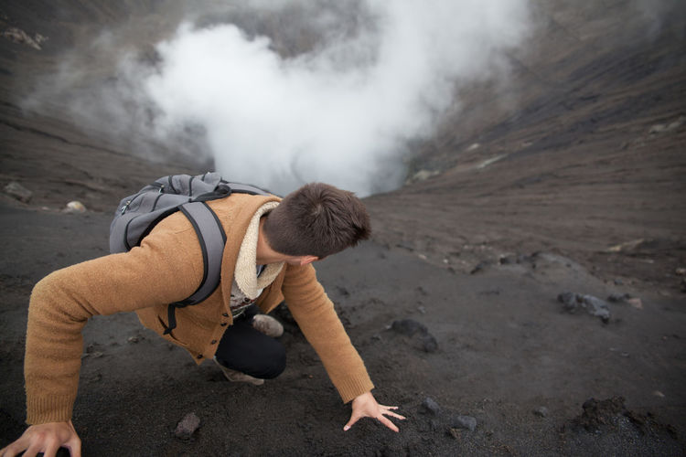 High Angle View Man Looking Down While Climbing Volcanic Mountain