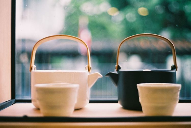 Close-Up Of Cups And Tea Kettles In Tray Against Window
