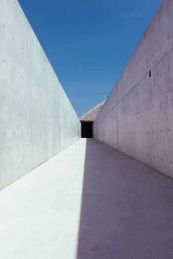 Alley Amidst Concrete Wall Against Blue Sky During Sunny Day