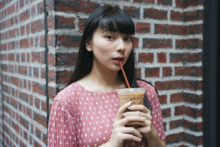 Portrait of young woman drinking glass against brick wall