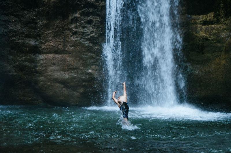 Man splashing water while jumping by waterfall
