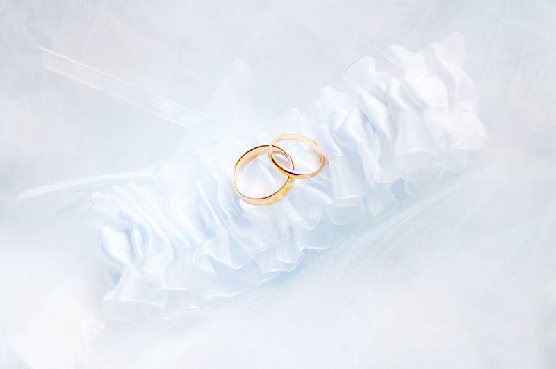 High angle view of wedding rings on silk fabric