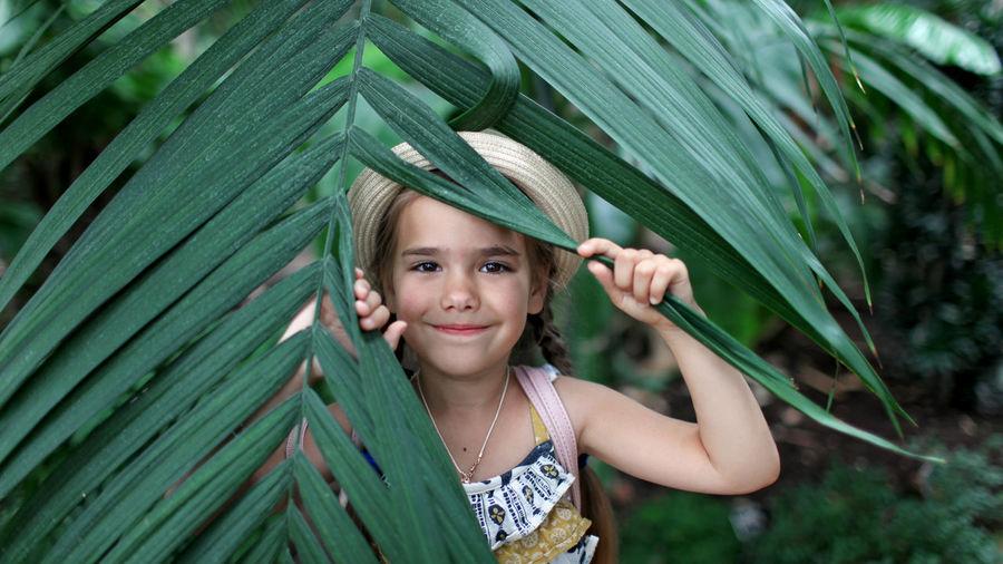 Girl holding leaf in forest