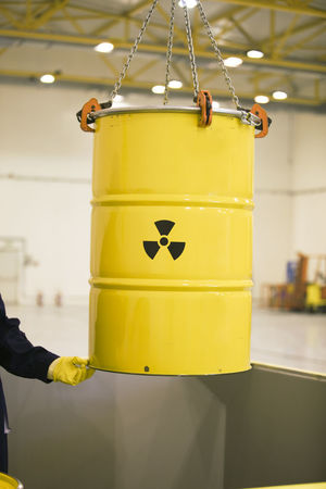 Lifting a barrel with nuclear waste. Radioactive waste management. Lifting Nuclear Power Radioactive Barrel Container Danger Environment Human Hand Nuclear Energy Nuclear Waste One Person Protection Radioactive Waste Safety Security Storage Symbol Threat Toxic Toxic Substance Warehouse Warning Sign Waste Disposal Waste Management Yellow Color