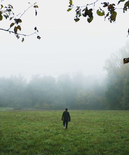 Rear view of man walking on field against sky