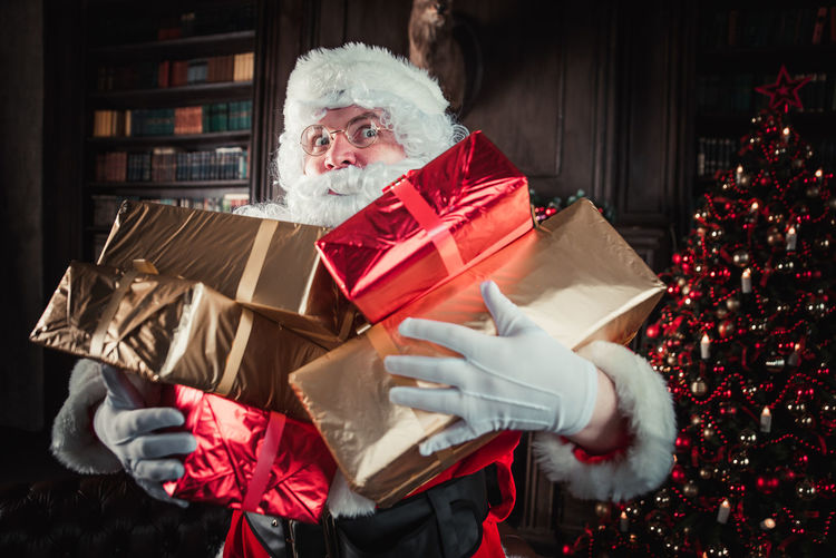 Man wearing santa claus costume holding christmas presents at home