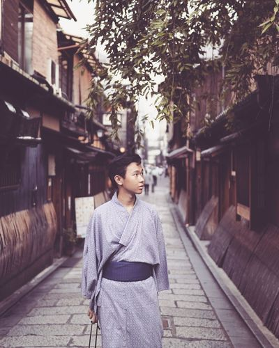 Thoughtful young man wearing traditional clothing while standing in alley
