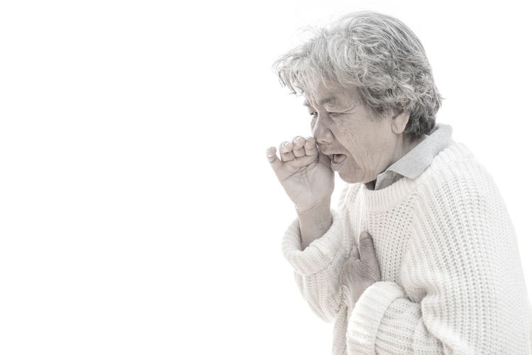 Close-Up Of Senior Woman Coughing Against White Background