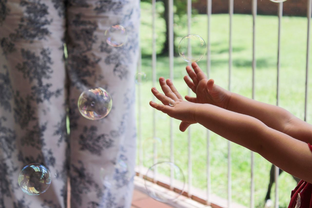 Kid hands with bubbles in balcony