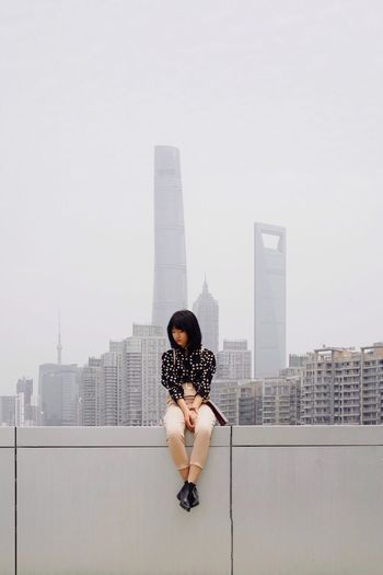 Woman sitting on wall in city against buildings and sky