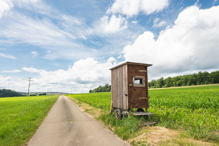Portable Toilet By Road On Field Against Sky