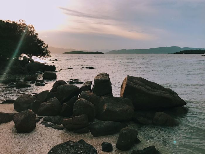 Stack of rocks on beach against sky during sunset