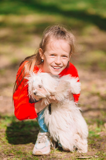 Cute girl with dog on field