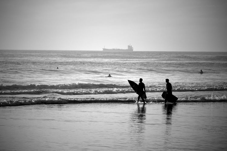 Surfers On Beach Against Sky