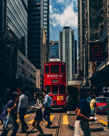 People on city street by modern buildings against sky