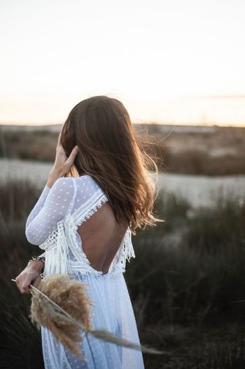 Wedding dress Woman Dresses Wedding Dress Sky Real People Lifestyles Women One Person Leisure Activity Water Nature Focus On Foreground Rear View Beauty In Nature Waist Up Copy Space Young Women Hairstyle Adult Standing Clear Sky Outdoors Sunset