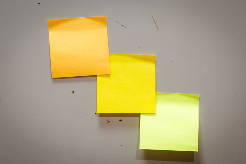 Close-up of yellow papers against wall