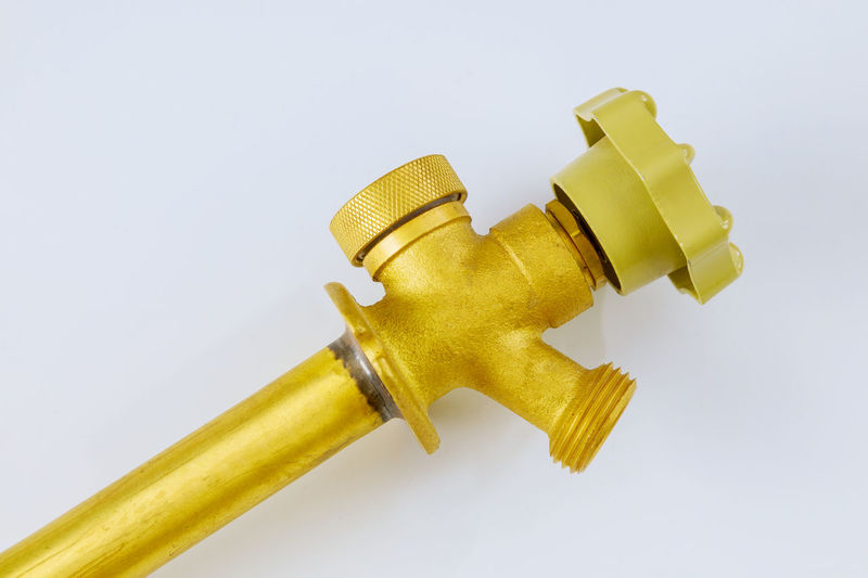 Close-up of yellow machine part against white background
