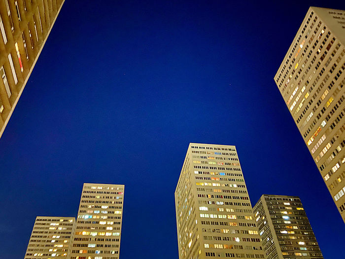 Low angle view of illuminated buildings against clear blue sky