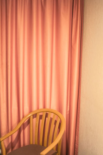 Empty Chair Against Curtain
