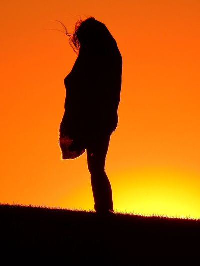 Silhouette person on field during sunset