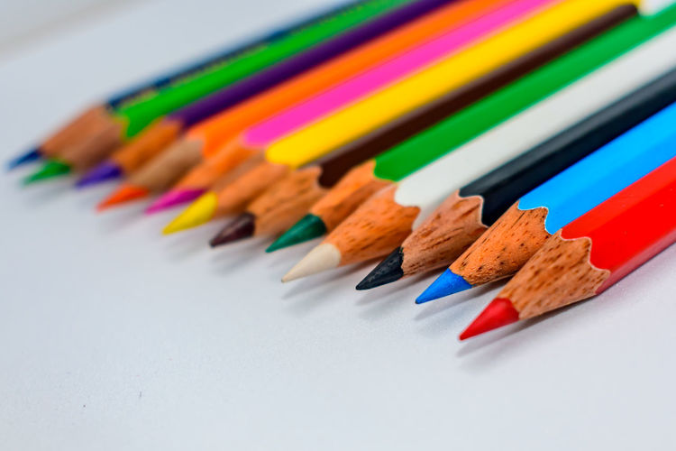 High angle view of colored pencils on white background