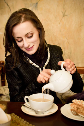 Close-Up Of Woman Pouring Tea From Teapot In Cup On Table