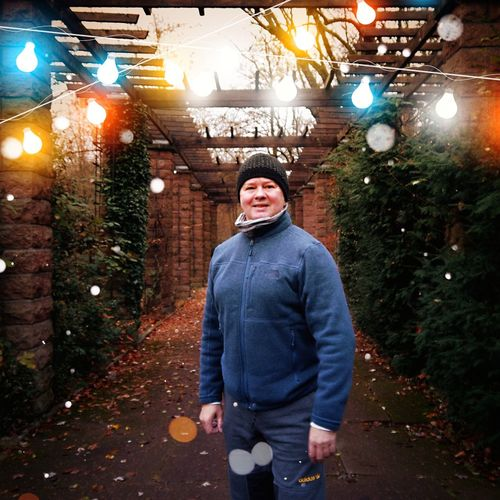 Portrait of man standing against illuminated lights