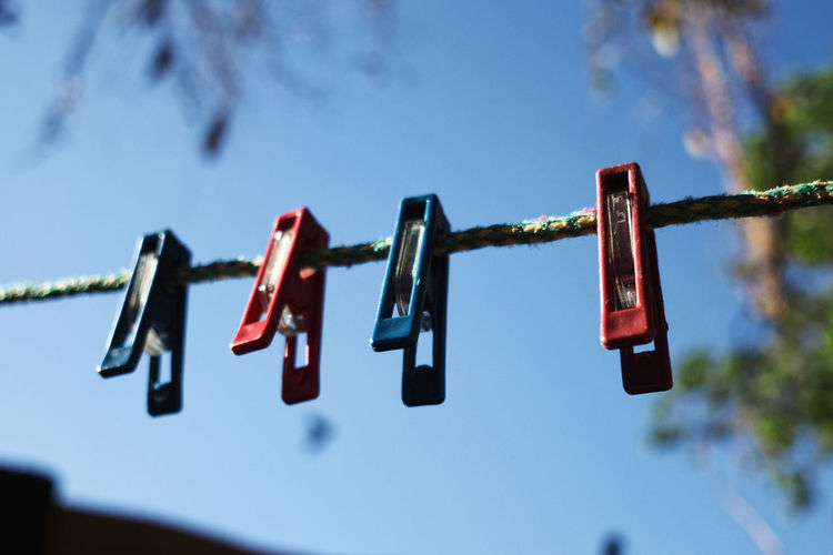 Low angle view of clothespins hanging on clothesline against blue sky