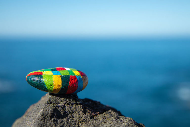 Close-up of multi colored pebble on rock against sea