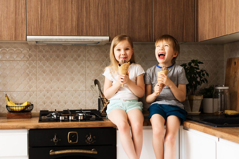 Siblings eating ice cream at home