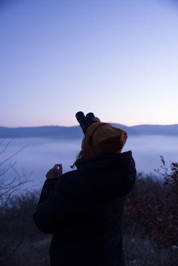 Rear view of a woman looking through binoculars