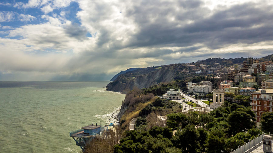 Scenic view of residential district and sea against cloudy sky