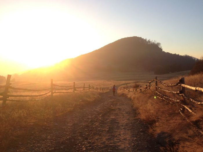 Dirt road along landscape at sunset